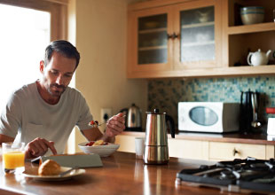 Image of a man eating fresh fruit for breakfast, while accessing the internet with mobile device.