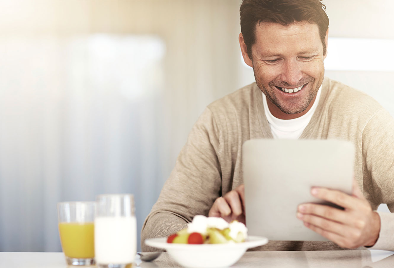 Photo of a man having breakfast, while using a tablet to access online banking.