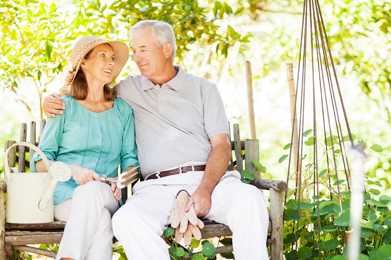 Photo of a retired couple sitting on a bench in the garden.