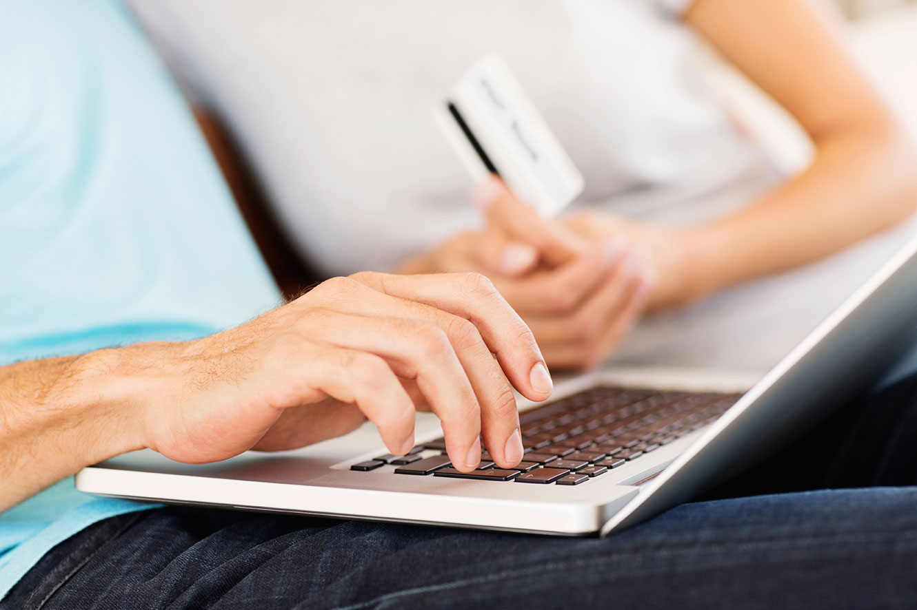 Photo of a couple using a laptop and a debit card to make a purchase online.